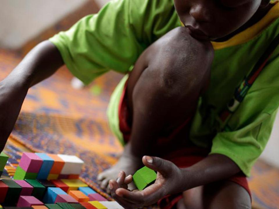 Menino preto, africano, brincando com blocos de madeira coloridos. Trabalhando a imaginação.