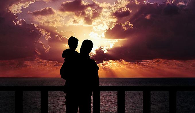 Educador, pai e criança olhando o mar